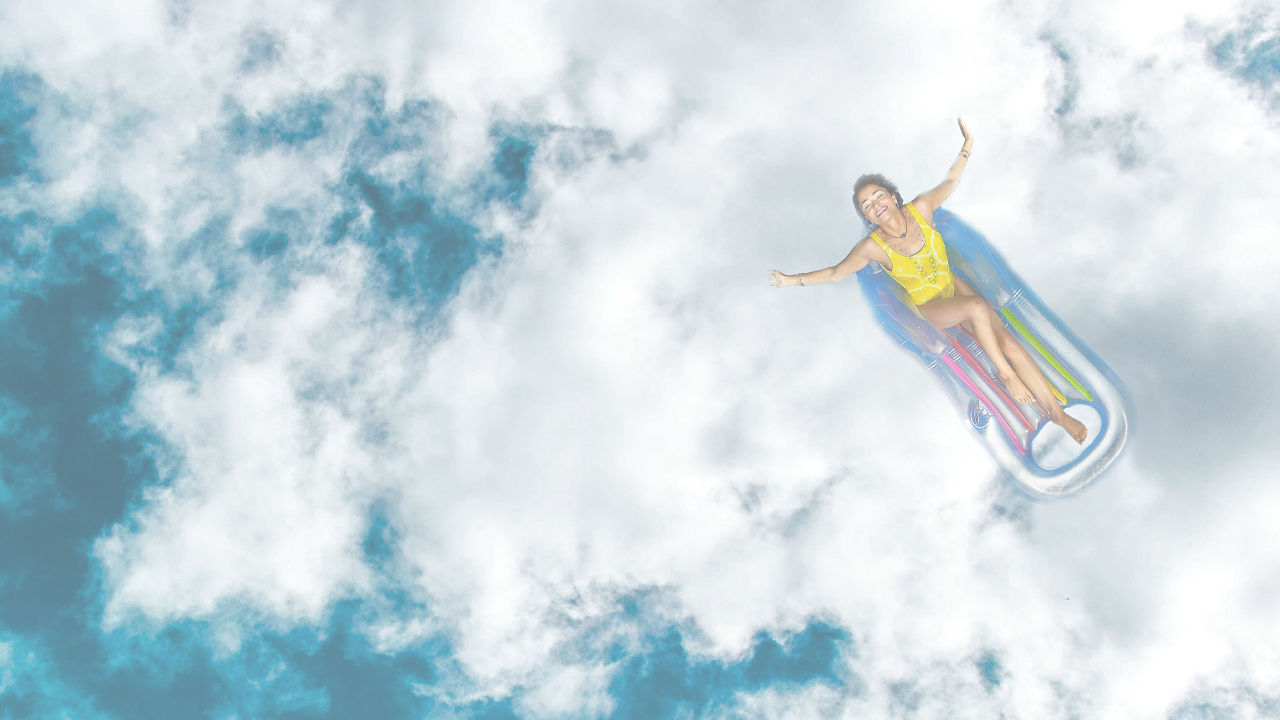 A happy woman on a pool floaty in the sky.